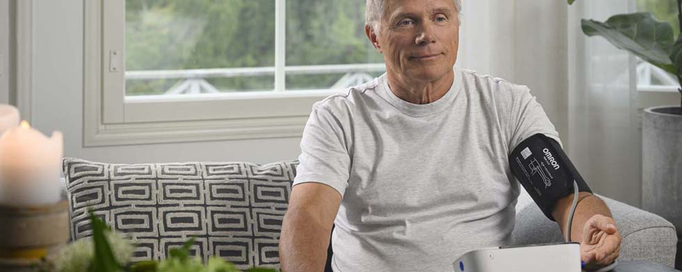 Mann auf Sofa misst Blutdruck